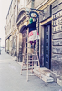720320-029-03 Lady painting a shop sign in Budapest (Hungary)